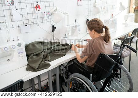 Young disable female in casualwear sitting in wheelchair by workplace inside contemporary workshop