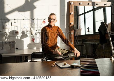 Young serious tailor with prosthesis instead of left leg sitting by workplace in front of camera