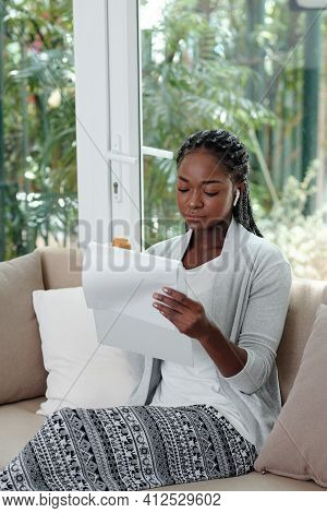 Young Black Woman In Loungewear Sitting On Sofa At Home., Eating Croissant And Reading Document
