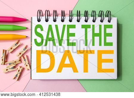 Save The Date. Text On White Notepad Paper. On A Colorful Background.