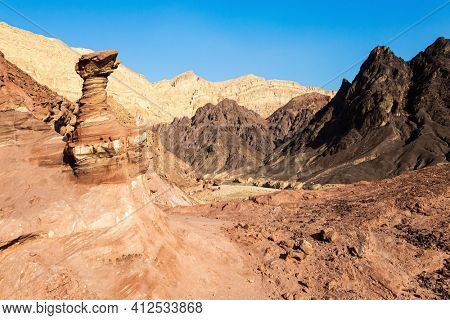 Bizarre forms of weathered sandstone in the mountains of Eilat. The rocks are composed of sandstones, igneous and volcanic rocks. Eilat Mountains. Multicolored landscape formations.