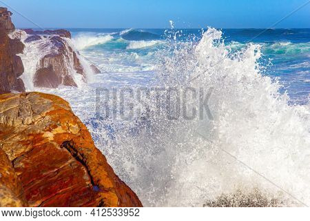 Powerful ocean surf. White foam of the ocean surf. South Africa. Cape of Good Hope at the southern tip of the Cape Peninsula. Bright sunny summer february day