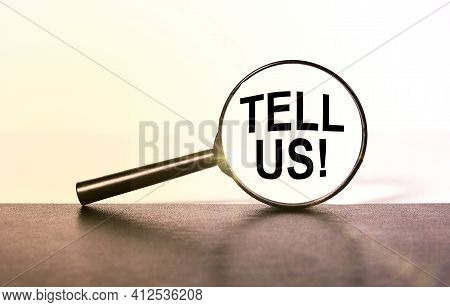 Tell Us. The Inscription In The Inside Of A Magnifying Glass On A White Background