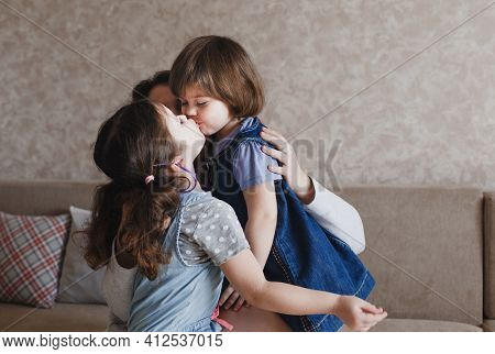 Two Little Girls Kiss Each Other On The Lips While Sitting On Their Mother S Lap