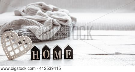 Still Life In Hygge Style With Wooden Word Home And Knitted Element. The Concept Of Home Comfort And