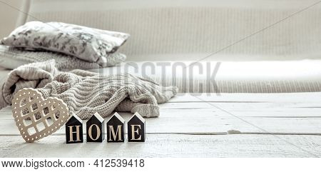 Still Life In Hygge Style With Wooden Word Home, Heart And Knitted Element. The Concept Of Home Comf