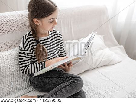 A Cute Little Girl Enthusiastically Examines A Book, Sitting On The Couch At Home. The Concept Of Ch