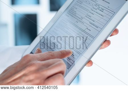 Doctor Is Filling Out A Patient Registration Form On A Digital Tablet.