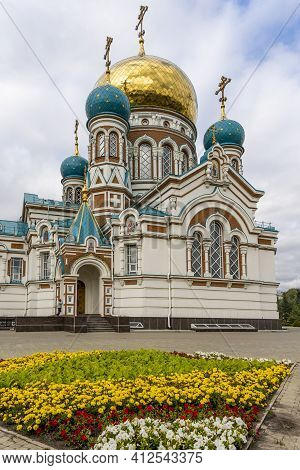 Omsk, Russia - September 13, 2019: Golden Dormition Cathedral In Omsk With Flowers In Front Of The C