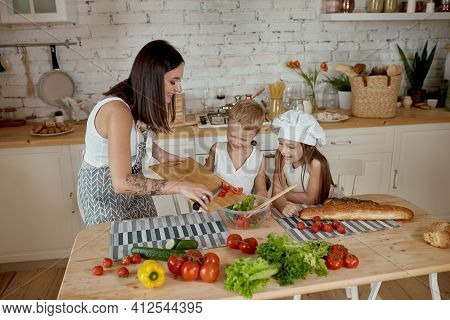 Children Learn How To Prepare A Salad In The Kitchen. Family Day Off, Lunch With Your Own Hands. Mom
