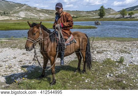 Khatgal, Mongolia - August 14, 2019: Mongolian Shepherd On Horseback With Hat And On The Steppe Of M