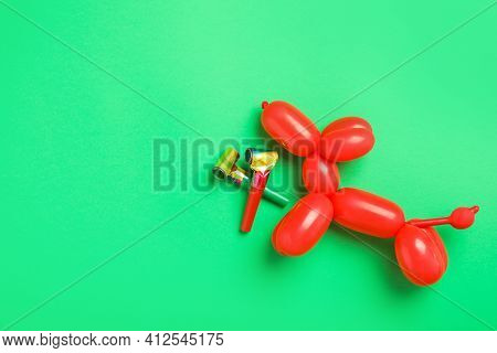 Party Blowers And Dog Figure Made Of Modelling Balloon On Green Background, Flat Lay. Space For Text