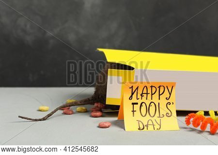 Words Happy Fool's Day And Box Of Corn Rings With Fake Rat's Tail On Light Grey Table. Space For Tex