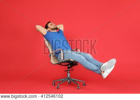 Young Man Relaxing In Comfortable Office Chair On Red Background