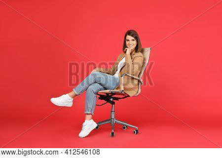 Young Woman Sitting In Comfortable Office Chair On Red Background
