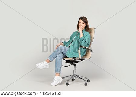 Young Woman Sitting In Comfortable Office Chair On Grey Background