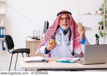 Old male arab doctor cardiologist working in the clinic