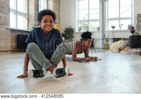 Happy little boy of African ethnicity standing on hands with his legs crossed against his mother