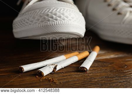 Woman Stepping On Pile Of Cigarettes, Closeup. Quitting Smoking Concept