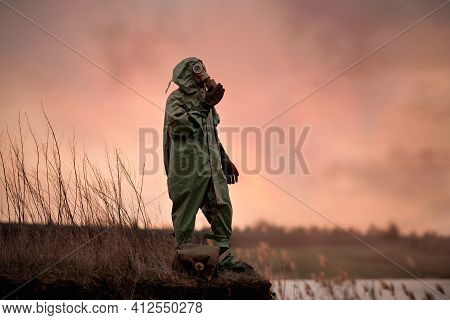 A Man In A Gas Mask And Protective Suit Stands On The Edge Of The Abyss.