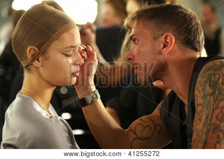 NEW YORK- SEPTEMBER 11: Make-up artist applying makeup to model backstage at the Blonds Collection f
