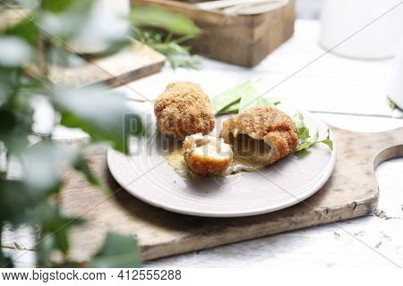 A Rustic Composition With Fried Chicken Kievs, Poultry Cutlets Whole And Halved, Served On A White P
