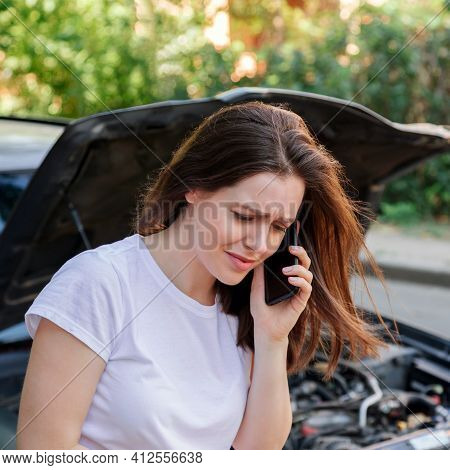 Scared Woman In Stress Holding Her Head After Auto Crash Calling To Auto Insurance For Help. Driver
