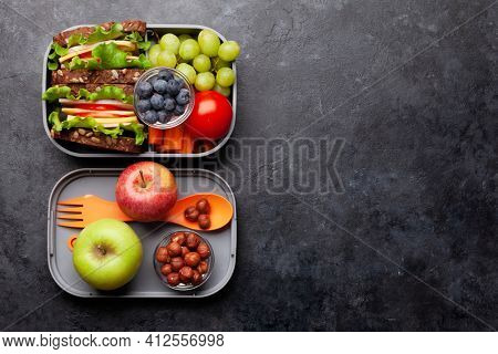 Healthy school lunch box with sandwich and fresh vegetables, water bottle, nuts and fruits. Top view flat lay with copy space