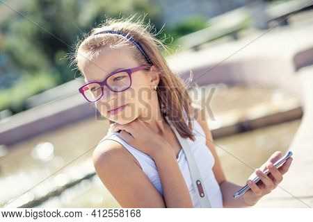 Young Pre-teen Blonde Girl Holds Mobile Phone In Her Hand Sitting On The Edge Of A Fountain On A Sun