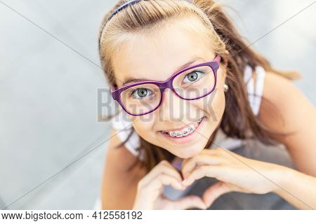 Young Preteen Girl In Glasses Wearing Braces Smiles At The Camera Showing Heart Shape With Her Hands