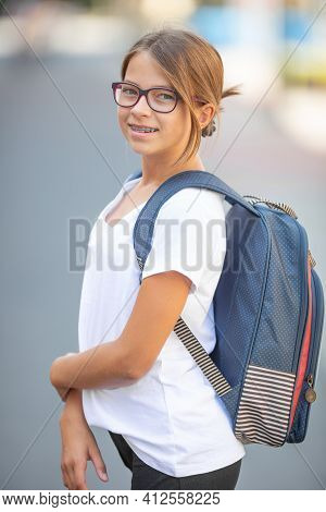 Young Teenage In Glasses And Braces Girl Wears School Bag And A White T-shirt.