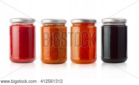 Front View Of Set Of Small Jam And Vegetable Jars In Different Colors Without Labels And Shiny Metal