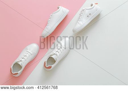 Male And Female White Sneakers On Color Pink Background. White Leather Shoes With Laces With Copy Sp