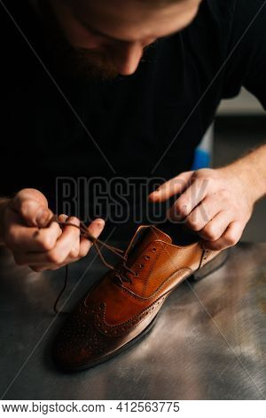 Close-up View Of Bearded Male Shoemaker Tying Laces On Repaired And Polished Light Brown Leather Sho