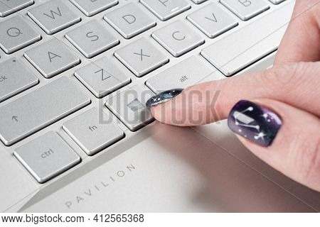 Sankt-petersburg, Russia, March 9, 2021: Laptop User Finger Pressing Windows Icon Key Button On Micr