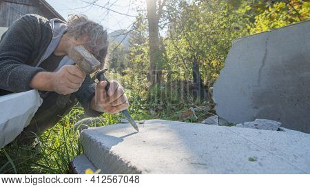Artist Carving In Stone With Great Precision Using A Mallet And Chisel.