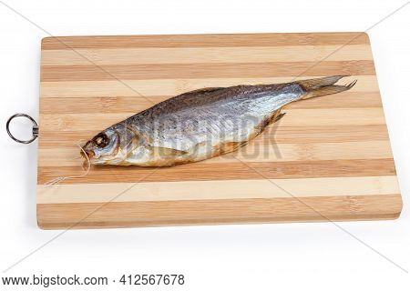 Salted And Air-dried Roach Fish On A Wooden Bamboo Cutting Board On A White Background