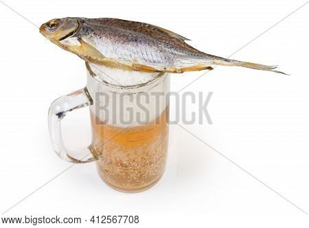 Salted And Air-dried Roach Fish Lies On A Beer Glass Partially Filled With Lager Beer On A White Bac
