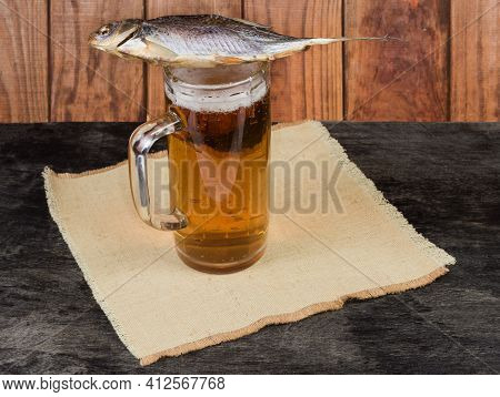 Salted And Air-dried Roach Fish Lies On A Beer Glass With Lager Beer On A Napkin On A Dark Table