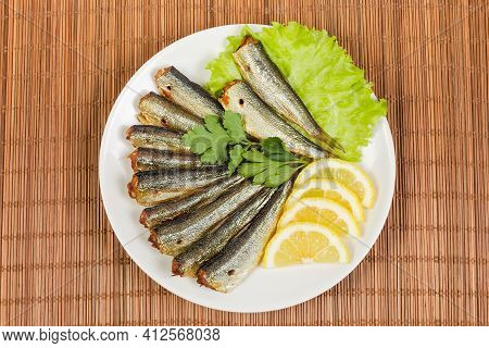 Smoked Headless Sprats And Lemon Slices Lie On Lettuce Leaves On A White Dish On A Bamboo Table Mat,