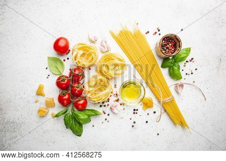 Pasta Background. Several Types Of Dry Pasta With Vegetables And Herbs On White Background. Free Spa