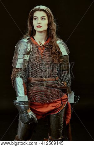 Portrait of a pensive female knight in armor of noble birth standing on a black background. History of the Middle Ages.