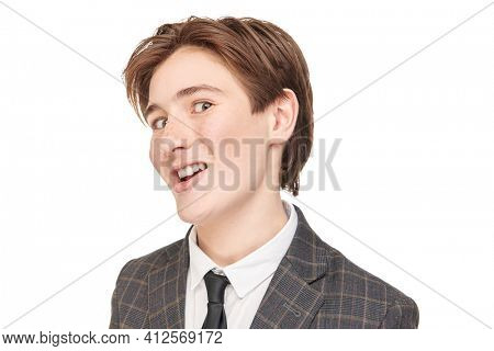 Strange boy. Teenager boy in school clothes makes funny faces. Studio portrait on a white background.