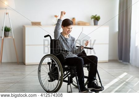 Excited Teen Boy In Wheelchair Holding Tablet Computer, Celebrating His Achievement Or Success, Winn