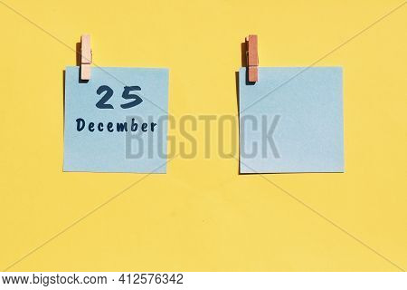 25 December. 25th Day Of The Month, Calendar Date. Two Blue Sheets For Writing On A Yellow Backgroun