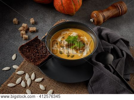 Pumpkin cream soup with pumpkin seeds and dried bread cubes. Lenten menu. Healthy, vegetarian food. Bowl with soup  and orange pumpkins on gray background.