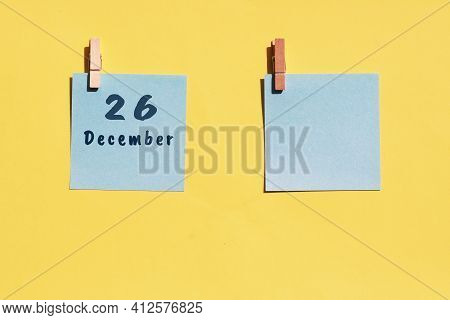 26 December. 26th Day Of The Month, Calendar Date. Two Blue Sheets For Writing On A Yellow Backgroun