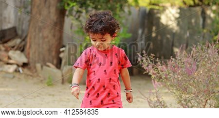 A Little Boy Of Indian Origin Wearing A Red Shirt Looking Down At The Ground, India.concept For Chil