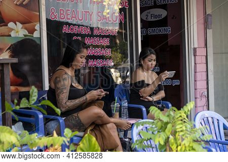 Female Masseuses Are Bored Waiting For Clients, And Chat On The Phone, Thailand, Phuket, December 31
