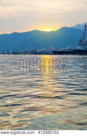 Shining water of The Bay of Kotor at sunset and Porto  Montenegro marina in the background. Tivat, Montenegro